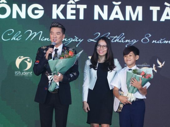 Ms. Tran Thuy Tram Quyen - Director of Branding & Communications Department gave flowers to Singer Dam Vinh Hung and Hieu Trung - parents and student of SNA.