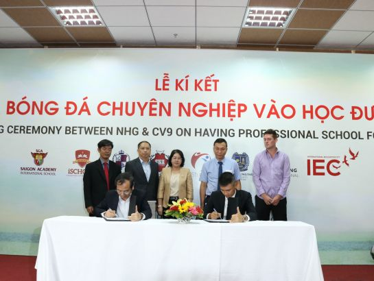 "Mr. Le Cong Vinh and Dr. Do Manh Cuong, Permanent Member of Education Council of NHG, sign the agreement to implement the project ""bring professional football to school"" with the witness of the representatives of VFF and the Ministry of Education and Training, HCMC."