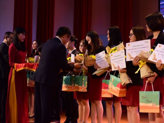 Dr. Dinh Quang Nuong gives flowers, Human books and gold heart badges to teachers of Teacher Award 2018 prize.