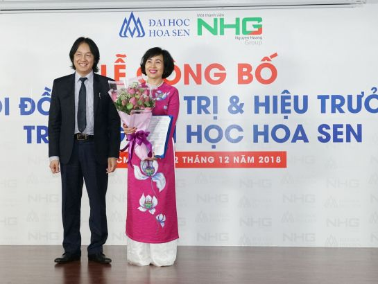 Mr. Hoang Quoc Viet gave flowers and decision of recognition of HSU president to Professor, Dr. Mai Hong Quy.
